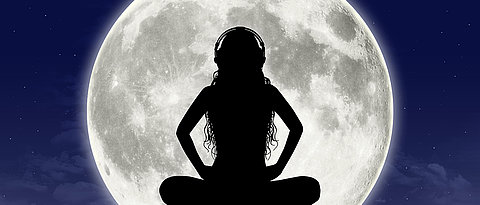 Women meditating in front of a full moon.